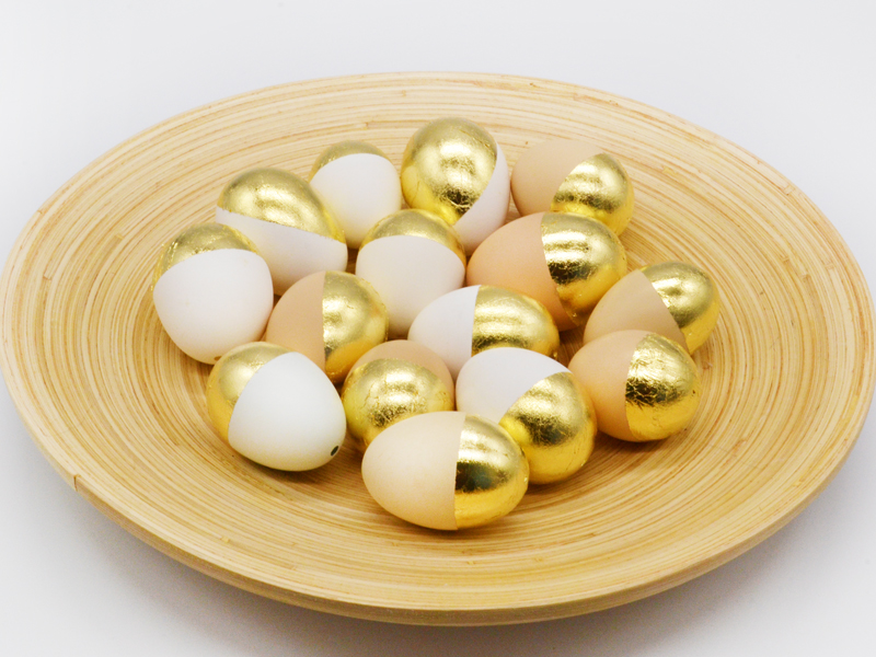 Eier mit Blattmetall auf Holzschale